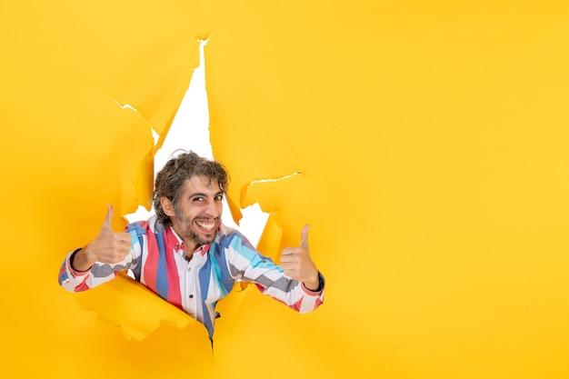 Gelukkige en emotionele jongeman die een goed gebaar maakt op een gescheurde gele papieren gatachtergrond