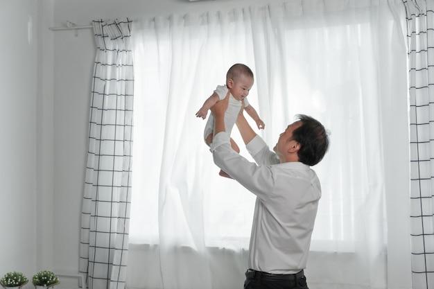 Gelukkige en familievader en peuterzoon die spelen lachen