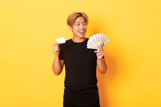 Gelukkige en gelukkige aziatische kerel die tevreden naar geld kijkt terwijl hij creditcard en contant geld laat zien, staande gele muur