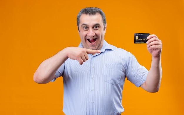 Gelukkige en glimlachende mens van middelbare leeftijd die blauw verticaal gestript overhemd draagt dat met wijsvingercreditcard richt