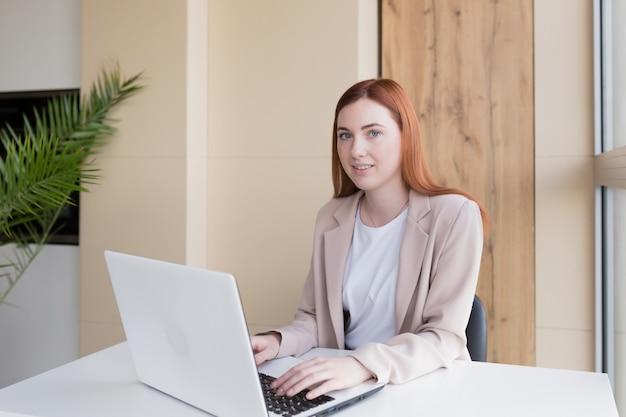 Gelukkige en glimlachende roodharige zakenvrouw die op de computer werkt om thuis te zitten