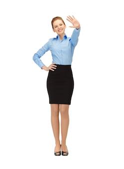 Gelukkige en glimlachende stewardess die een groetgebaar maakt