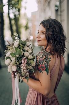 Gelukkige en glimlachende vrouw met boeket bloemen in een roze trouwjurk en een trouwring