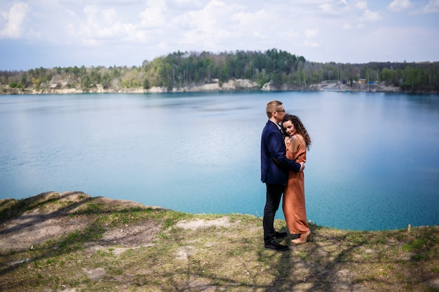 Gelukkige en jonge pasgetrouwden gaan hand in hand en lachen, op de achtergrond van een meer en een groene weide. bruidegom en mooie bruid met krullend haar lopen in de wei. vrolijke zomerdag