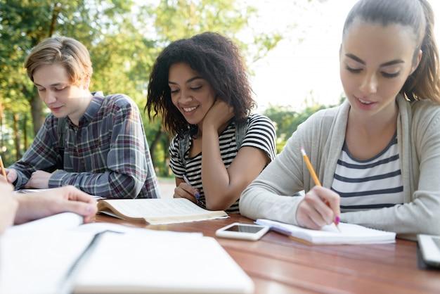 Gelukkige en jongerenvrienden die in openlucht zitten bestuderen