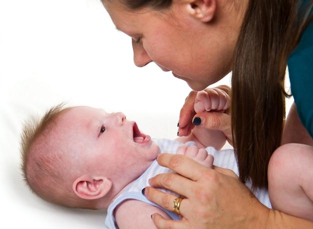 Gelukkige en moeder en baby die spelen lachen.