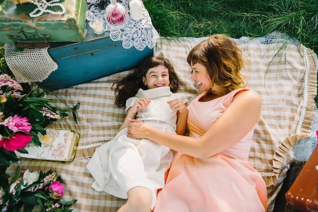 Gelukkige en moeder en dochter die terwijl het liggen op een deken in de zomer spelen glimlachen