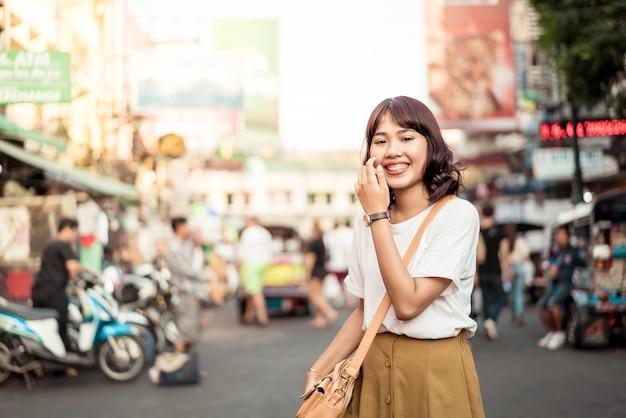 Gelukkige en mooie aziatische vrouw die bij khao sarn road, thailand reist