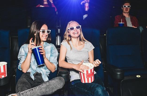 Gelukkige en mooie meisjes zitten in de bioscoopzaal en kijken naar film. blond meisje kijkt recht en glimlacht terwijl haar vriend haar glimlachend aankijkt en een grote kop cola vasthoudt