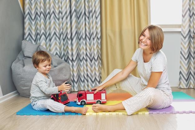 Gelukkige en mooie moeder en kindfamilie die samen speelgoedauto's spelen in de kinderkamer