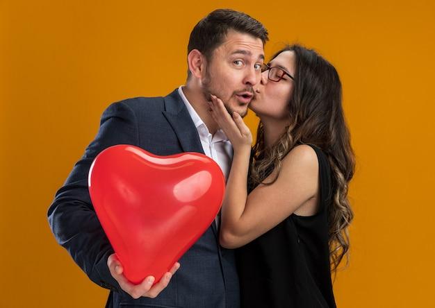 Gelukkige en mooie paarvrouw die haar vriendje kust met rode ballon in hartvorm die valentijnsdag viert over oranje muur