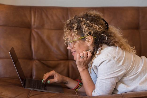 Gelukkige en ontspannen schattige vrouw thuis gebruikt laptop op de bank thuis - alternatieve en moderne mensen in slim werk - vrouw genieten van webpagina's en online winkelen - draadloos verbindingsconcept