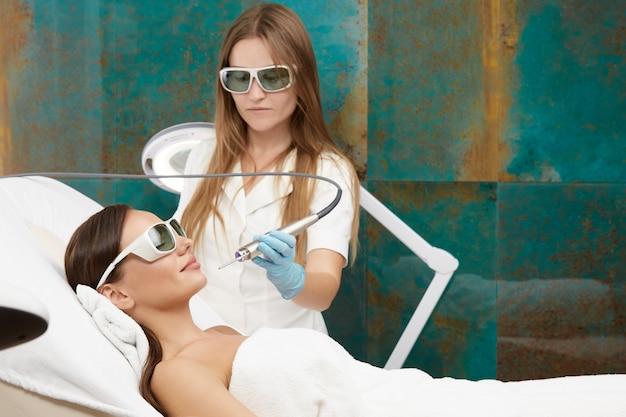Gelukkige en ontspannen vrouw die gezichtsbehandeling met laser ontvangt voor haarverwijdering die een bril draagt