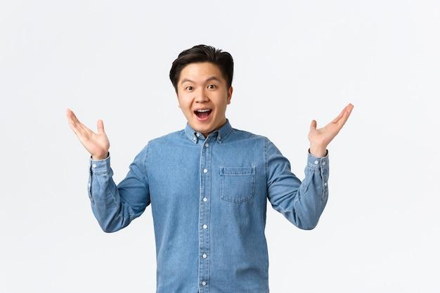 Gelukkige en opgewonden aziatische verraste man ontvangt geweldig nieuws, steekt zijn handen opzij en glimlacht verbaasd, prees geweldig werk, zegt gefeliciteerd, verheugt zich op een witte achtergrond.