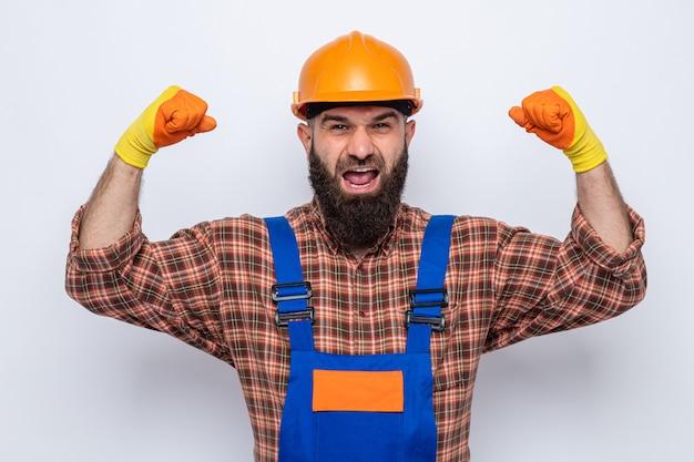 Gelukkige en opgewonden bebaarde bouwman in bouwuniform en veiligheidshelm die rubberen handschoenen draagt en vuisten opheft als een winnaar