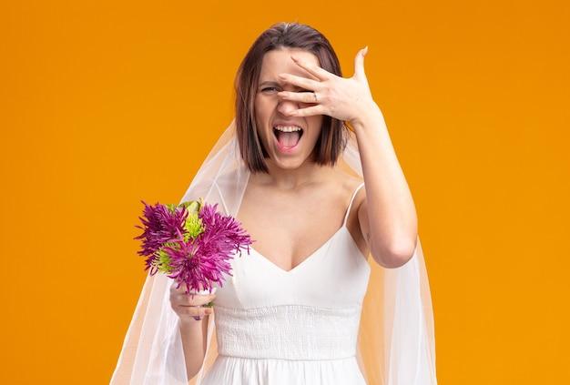 Gelukkige en opgewonden bruid in mooie trouwjurk met bruiloft bloemboeket schreeuwende ogen bedekken met palm