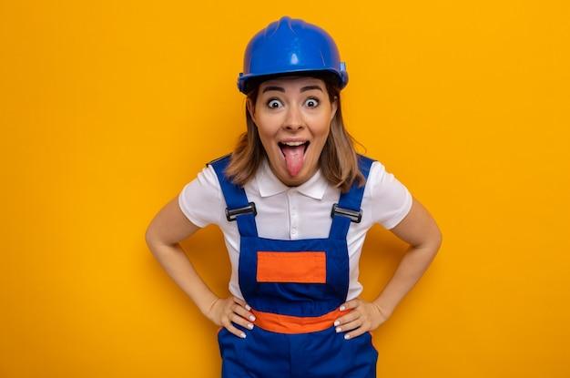 Gelukkige en opgewonden jonge bouwvrouw in bouwuniform en veiligheidshelm die tong uitsteekt die over oranje muur staat