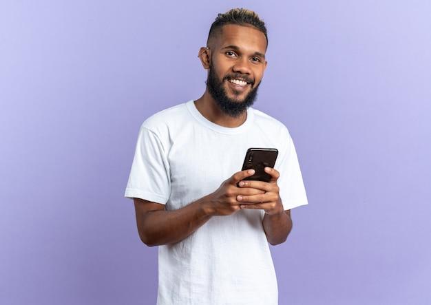 Gelukkige en positieve afro-amerikaanse jonge man in wit t-shirt met smartphone kijkend naar camera glimlachend vrolijk staande over blauwe achtergrond