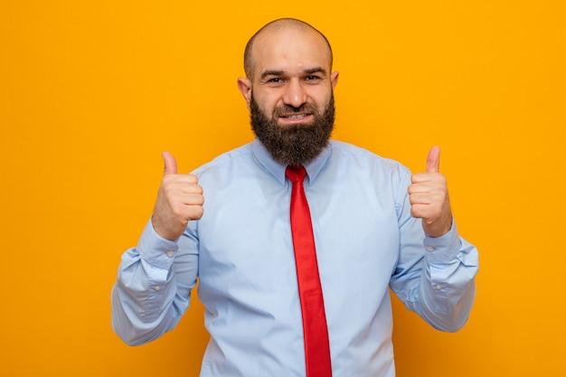 Gelukkige en positieve bebaarde man in rode stropdas en hemd die naar de camera kijkt die vrolijk lacht en duimen laat zien die over een oranje achtergrond staan