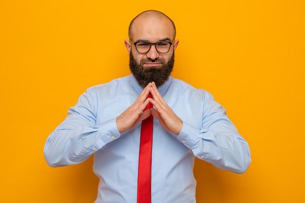 Gelukkige en positieve bebaarde man in rode stropdas en shirt met een bril die handen bij elkaar houdt, wachtend op iets dat over een oranje achtergrond staat