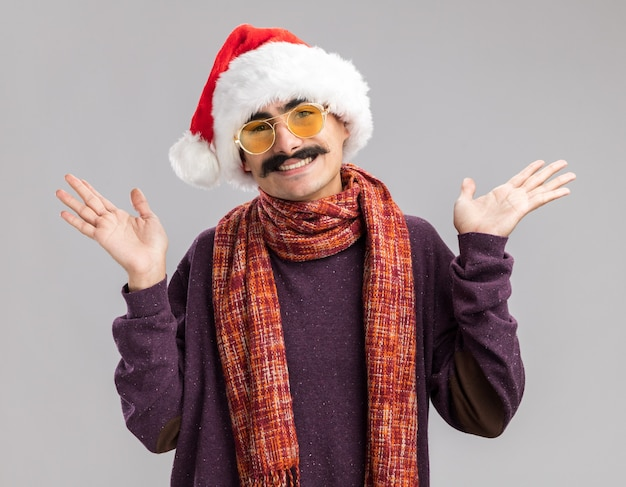 Gelukkige en positieve besnorde man met kerstmuts en gele bril met warme sjaal om zijn nek vrolijk glimlachend met opgeheven armen over witte muur
