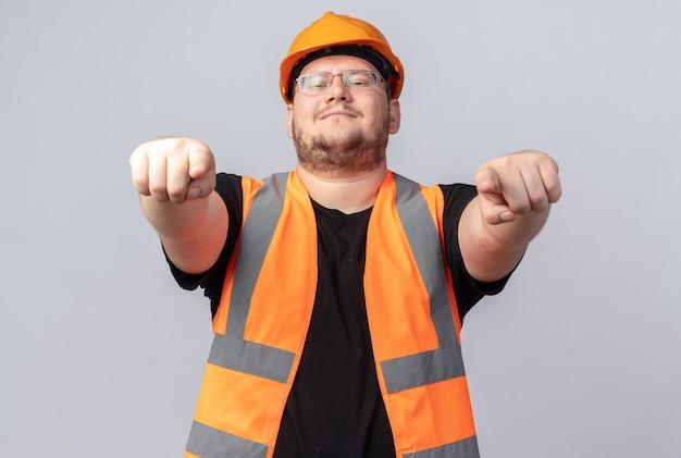Gelukkige en positieve bouwman in bouwvest en veiligheidshelm wijzend met wijsvingers naar camera glimlachend vrolijk staande over wit
