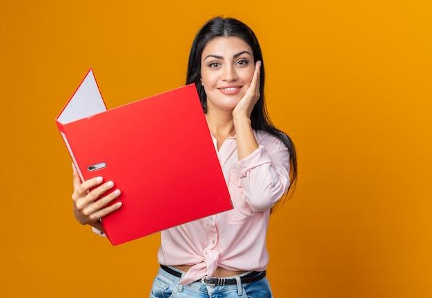 Gelukkige en positieve jonge mooie vrouw in vrijetijdskleding die een map vasthoudt die vriendelijk glimlacht en op oranje staat