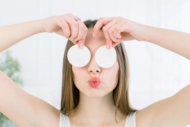 Gelukkige en positieve jonge mooie vrouw met open schouders die haar ogen behandelen met katoenen stootkussens en kuslippen op een lichte achtergrond tonen. huidverzorging en schoonheid concept