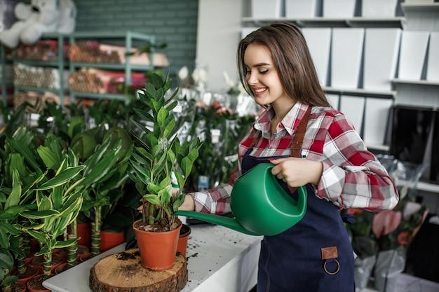 Gelukkige en positieve jonge vrouw die in de kas werkt en geniet van het water geven van prachtige bloemen