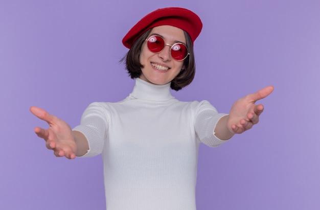 Gelukkige en positieve jonge vrouw met kort haar in witte coltrui die baret en rode zonnebril draagt