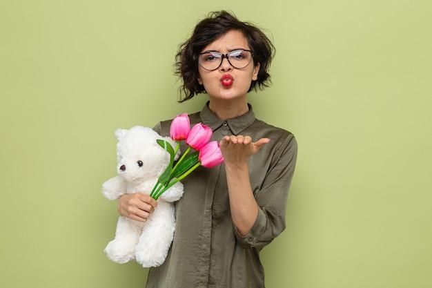 Gelukkige en positieve vrouw met kort haar met boeket tulpen en teddybeer kijkend naar camera die een kus blaast die internationale vrouwendag 8 maart viert en zich over groene achtergrond bevindt