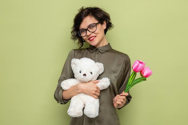 Gelukkige en positieve vrouw met kort haar met boeket tulpen en teddybeer kijkend naar camera glimlachend vrolijk internationale vrouwendag 8 maart vieren staande over groene achtergrond