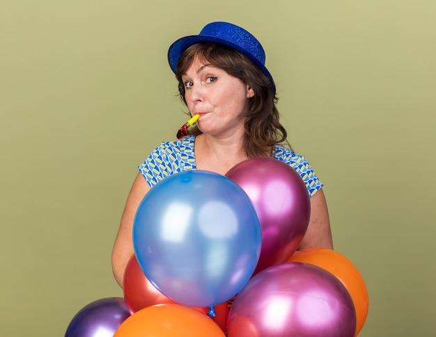 Gelukkige en positieve vrouw van middelbare leeftijd in feestmuts met een bos kleurrijke ballonnen die op een fluitje blazen en een verjaardagsfeestje vieren dat over de groene muur staat