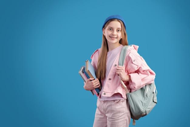 Gelukkige en succesvolle tienerstudent in vrijetijdskleding die rugzak en stapel boeken draagt terwijl hij naar school gaat