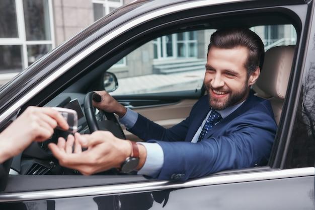 Gelukkige en succesvolle vrolijke en stijlvolle jonge zakenman in volledig pak neemt een sleutel