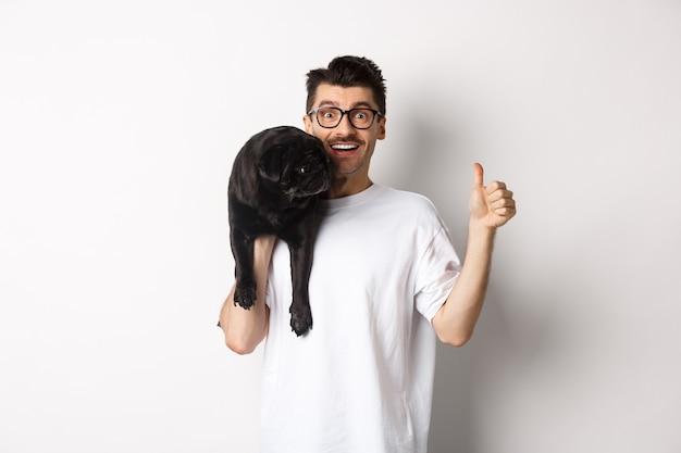 Gelukkige en tevreden hondeneigenaar die duim omhoog laat zien, schattige zwarte mopshond op de schouder houdt, huisdierproducten aanbeveelt, staande op een witte achtergrond