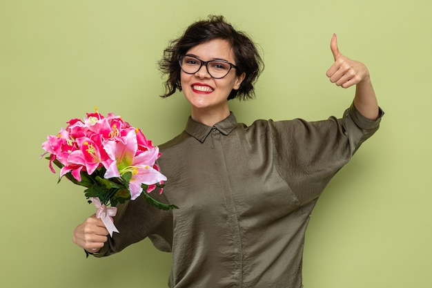 Gelukkige en tevreden vrouw met kort haar met boeket bloemen kijkend naar camera glimlachend vrolijk duimen opdagen vieren internationale vrouwendag 8 maart staande over groene achtergrond