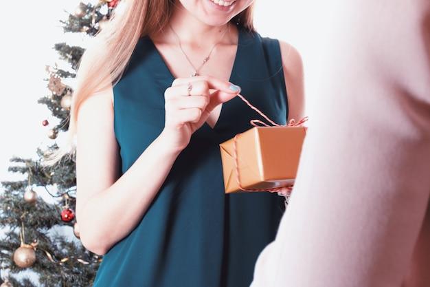 Gelukkige en verraste vrouw die een gift ontvangt. vrolijk kerstfeest