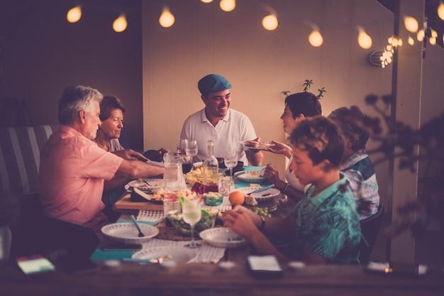 Gelukkige en vriendelijke mensen die samen eten thuis of in een restaurant in vriendschap - familie met verschillende leeftijden en generaties mannen en vrouwen die genieten van eten aan tafel