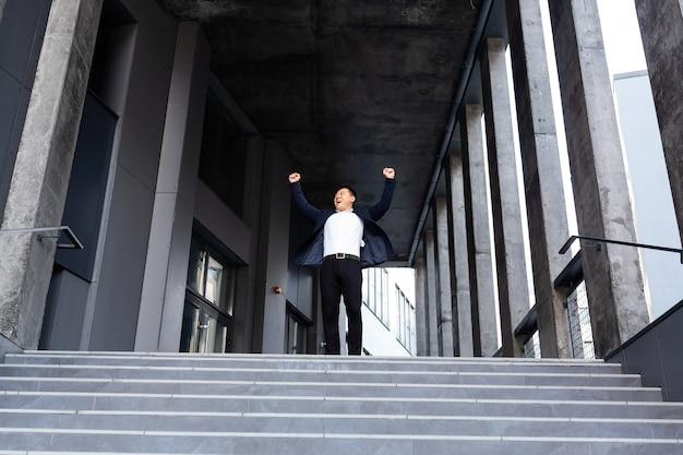Gelukkige en vrolijke aziatische zakenman die handen vasthoudt en zich verheugt in overwinning en succes in de buurt van het vooraanzicht van het kantoorcentrum