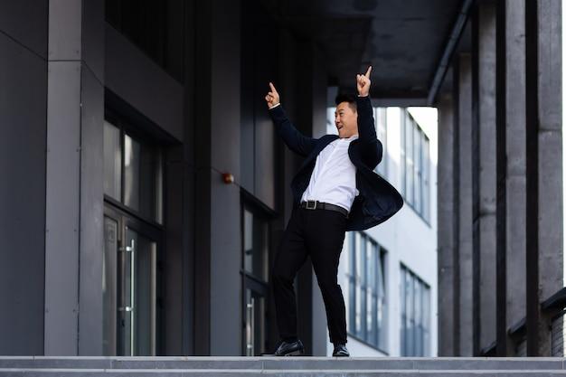 Gelukkige en vrolijke aziatische zakenman die in de buurt van het kantoor danst, verheugt zich in overwinning en succes Premium Foto