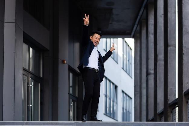 Gelukkige en vrolijke aziatische zakenman die in de buurt van het kantoor danst, verheugt zich in overwinning en succes