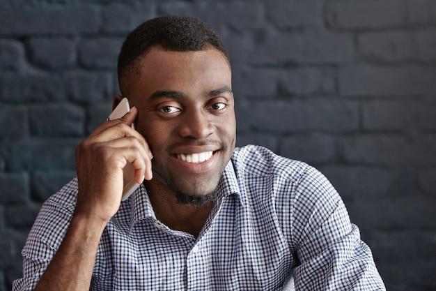 Gelukkige en vrolijke jonge afrikaans-amerikaanse zakenman die vreugdevol glimlacht terwijl het hebben van telefoongesprek