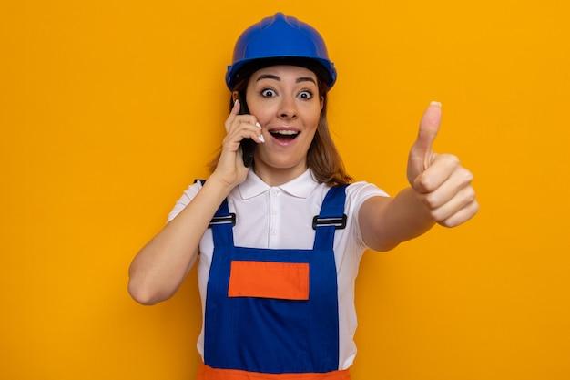 Gelukkige en vrolijke jonge bouwvrouw in bouwuniform en veiligheidshelm die kijkt terwijl ze op een mobiele telefoon praat met duimen omhoog