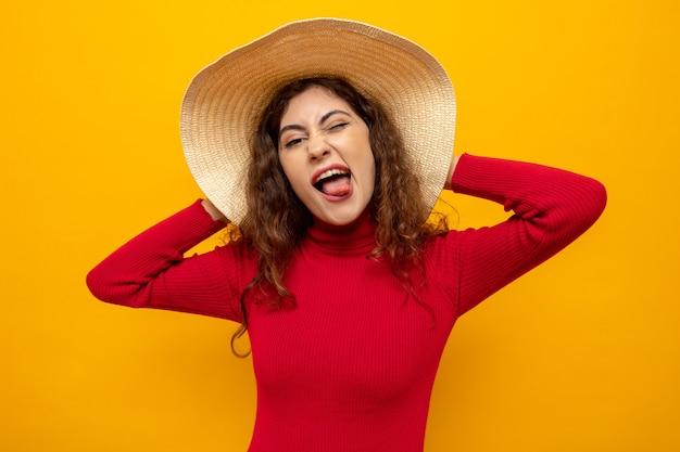 Gelukkige en vrolijke jonge mooie vrouw in rode coltrui in zomerhoed die naar voren kijkt en plezier heeft terwijl ze tong uitsteekt die over oranje muur staat