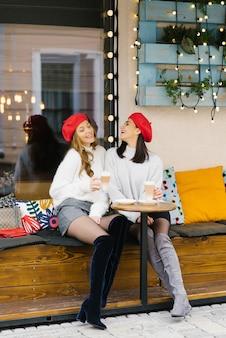 Gelukkige en vrolijke vriendinnen in rode baretten drinken koffie aan de tafel van het straatcafé. een sterke vriendschap tussen twee jonge vrouwen. leuk tijdverdrijf