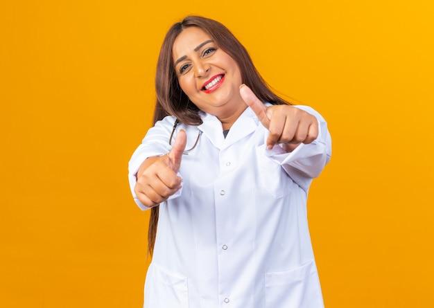 Gelukkige en vrolijke vrouw van middelbare leeftijd arts in witte jas met stethoscoop die er glimlachend uitziet met duimen omhoog