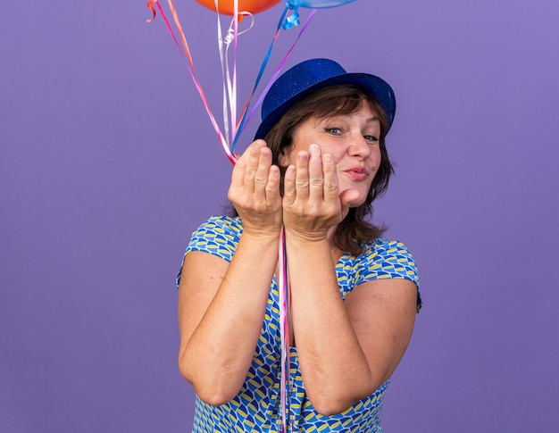 Gelukkige en vrolijke vrouw van middelbare leeftijd in feestmuts met een bos kleurrijke ballonnen die een kus blazen om een verjaardagsfeestje te vieren dat over de paarse muur staat