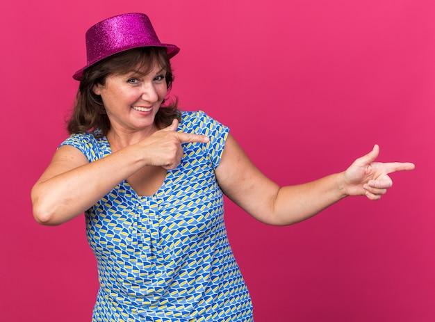 Gelukkige en vrolijke vrouw van middelbare leeftijd met een feestmuts die met wijsvingers naar de zijkant wijst en breed glimlacht