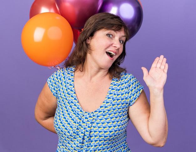 Gelukkige en vrolijke vrouw van middelbare leeftijd met een stel kleurrijke ballonnen glimlachend zwaaiend met de hand